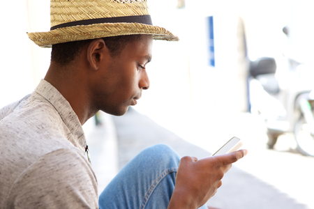 Close up portrait of a cool black guy looking at mobile phone Stock Photo