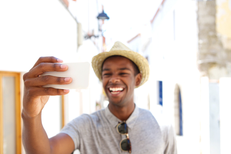 black guy: Happy young man taking selfie on vacation