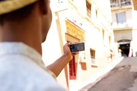 african man: Young man walking around town taking selfie