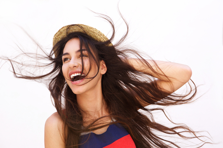 fashionable female: Portrait of a smiling young woman with long hair blowing in the wind