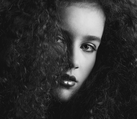 a close up: Close up black and white portrait of a a beautiful female fashion model with curly hair Stock Photo