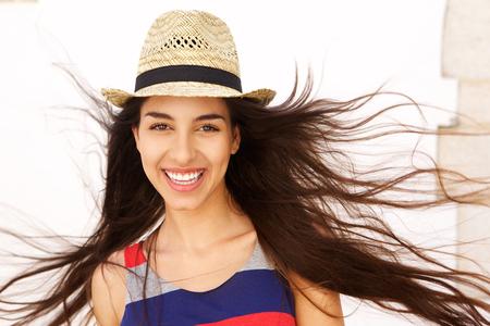 capelli lunghi: Primo piano ritratto di una giovane donna spensierata sorridente con i capelli lunghi che soffia nel vento