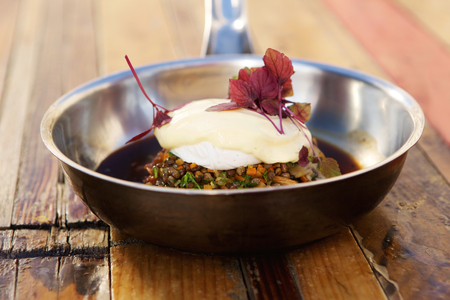 stew pan: Vegetarian dish of lentil stew and poached egg on a wooden table