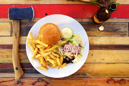 fry: Top view dinner of burger, fries with a salad and beer Stock Photo