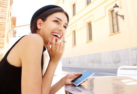 lachendes gesicht: Side Portr�t einer jungen Frau mit Handy lachen