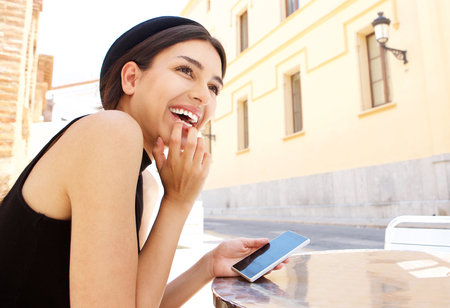 teenagers laughing: Side portrait of a young woman laughing with mobile phone