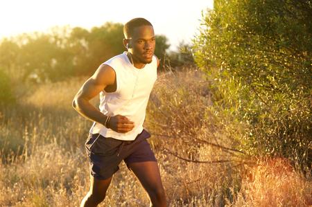 hombres negros: Retrato de un hombre afroamericano de ajuste que se ejecuta fuera