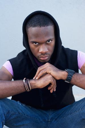 cool guy: Portrait of a cool black guy sitting with hood sweatshirt