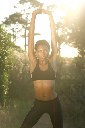 Portrait of a fit african american woman stretching exercise outdoors photo