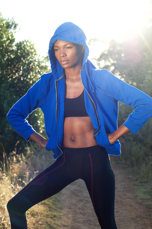 Portrait of a fitness woman standing outside with blue sweatshirt photo