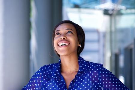 mujer sola: Cerca de retrato de una mujer de negocios africano riendo y mirando hacia arriba