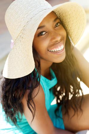 Close-up portret van een jonge Afro-Amerikaanse vrouw lachen met zonnehoed