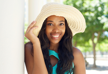 modelos negras: Cerca de retrato de una atractiva mujer afroamericana sonriente con sombrero para el sol