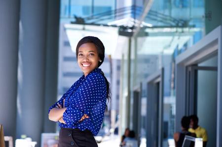 femme africaine: Portrait d'une femme d'affaires africaine souriant, les bras croisés