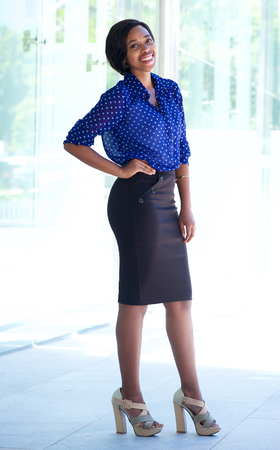 Full length portrait of an smiling african american business woman standing outside