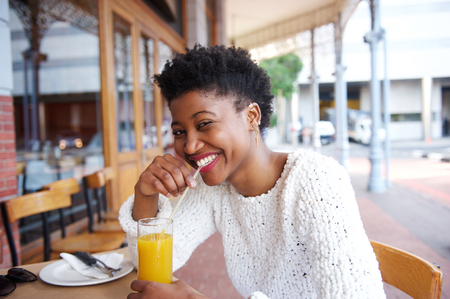 alone person: Close up portrait of a smiling black girl drinking orange juice at outdoor cafe