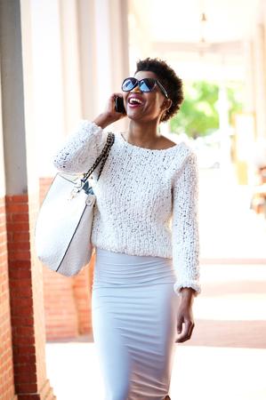 persone nere: Ritratto di una giovane donna allegra camminare e parlare al telefono cellulare