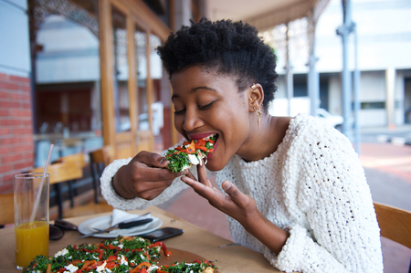 Portrait of an african american woman eating pizza at outdoor restaurant Standard-Bild