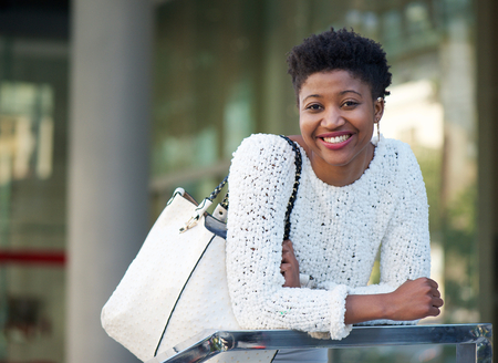 african american woman: Portrait of a smiling african american woman with bag Stock Photo