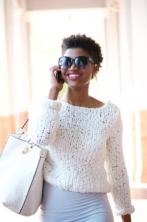 modelos negras: Retrato de una mujer joven y atractiva caminando y hablando por teléfono móvil