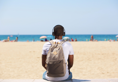 back: Portrait from behind of a young man sitting by the beach listening to music on headphones