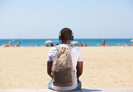 persons back: Retrato de detrás de un joven sentado en la playa escuchando música en los auriculares Foto de archivo