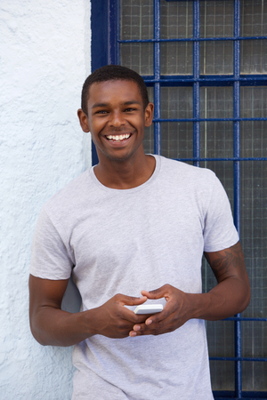guy: Portrait of a smiling african american guy with cellphone