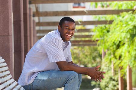 Zij portret van een jonge zwarte man buiten zitten lachen