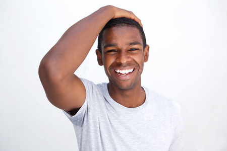Close up portrait of a laughing african american man posing against white background
