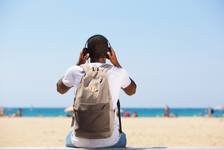 listening back: Young man sitting by beach with bag listening to music on headphones Stock Photo