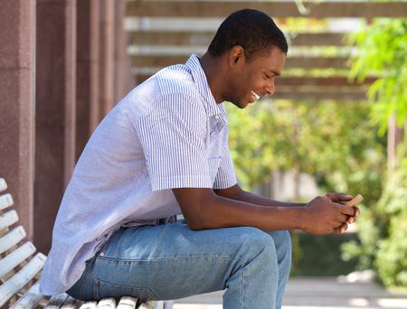 black guy: Retrato lateral de un muchacho negro fresco que mira el tel�fono celular