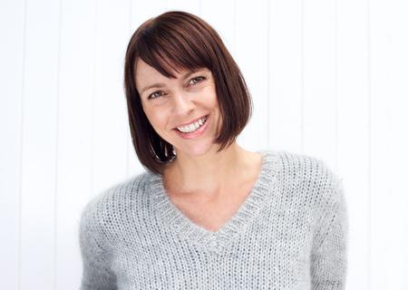 Close-up portret van een aantrekkelijke oudere vrouw lachend tegen een witte achtergrond Stockfoto