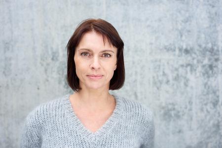 Close-up portret van een mooie oudere vrouw met bruin haar staande tegen de grijze achtergrond Stockfoto