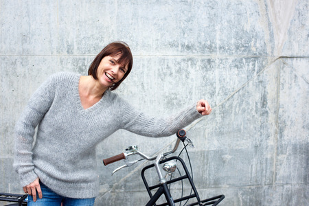mujeres maduras: Retrato de una mujer mayor alegre con la bicicleta Foto de archivo
