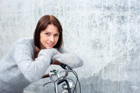 beautiful middle aged woman: Close up portrait of an attractive older woman smiling with bike Stock Photo