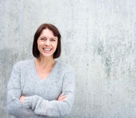 灰色の背景に対して笑みを浮かべて自信がある年上の女性の肖像画