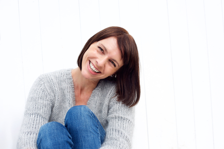 Close up portrait of a smiling middle aged woman sitting against white wall Stock Photo