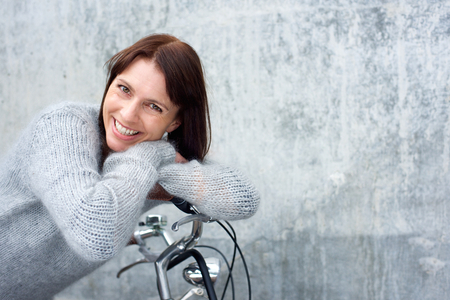Portrait of a middle aged woman smiling and leaning on bicycle Stock Photo