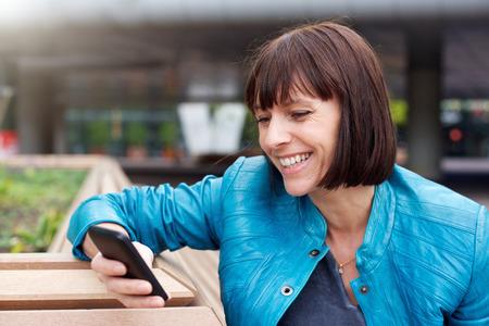 mujer alegre: Cerca de retrato de una mujer madura sonriendo y mirando al teléfono celular Foto de archivo