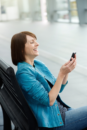 beautiful middle aged woman: Portrait of a beautiful middle aged woman looking at mobile phone Stock Photo