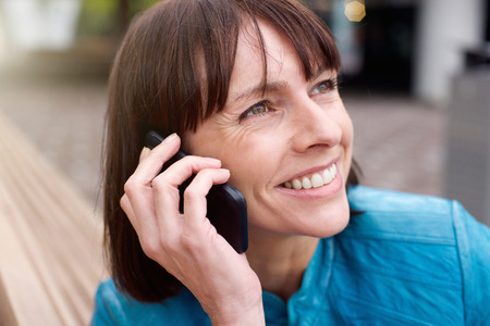 adult woman: Close up portrait of a beautiful older woman smiling with mobile phone outside Stock Photo