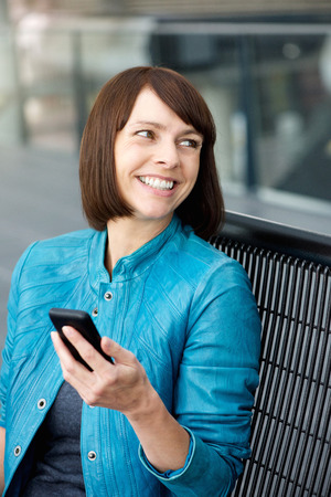 beautiful middle aged woman: Portrait of a middle aged woman smiling with cell phone Stock Photo