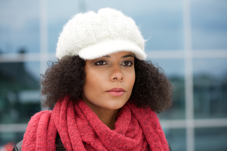 young woman face: Close up portrait of a young african american woman with winter hat and scarf Stock Photo