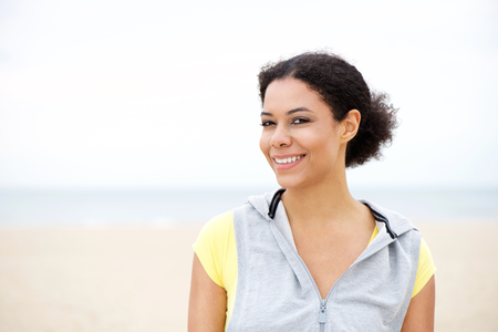 casual woman: Close up portrait of a fit african american woman smiling at the beach