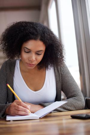 Close up Portrait einer jungen African American weiblichen Studenten schriftlich in Buch