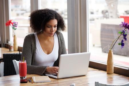 cafe internet: Retrato de una mujer joven afroamericano sentado en el café con el ordenador portátil a escribir su blog