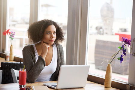 american content: Portrait of an attractive african american woman with laptop looking out of window