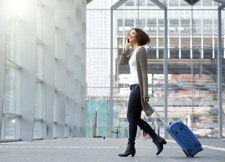 reizen: Full length kant portret van een reizende jonge vrouw met mobiele telefoon en koffer