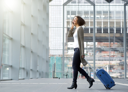 Full length side portrait of a traveling young woman with mobile phone and suitcase. Stock Photo