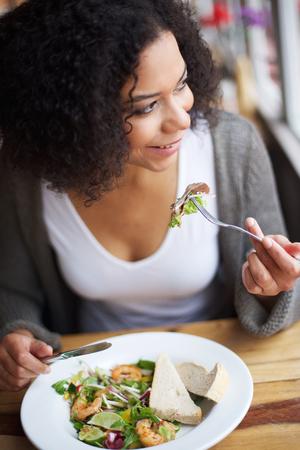 mujeres negras: Retrato de una mujer afroamericana sonriente comer en el restaurante Foto de archivo